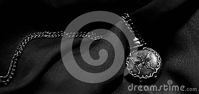 Pocket-watch with a butterfly engraving and a metal chain Stock Photo