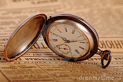 Pocket watch on vintage newspaper