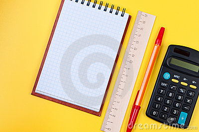 Pocketbook and calculator on yellow background.