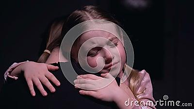 Poco niño femenino que abraza a la madre y que llora, víctimas de la violencia doméstica, miedo metrajes