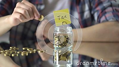 Podatku słowo pisać nad szklany słój z pieniądze, oficjalny wydarcia pojęcie, gospodarka zbiory wideo