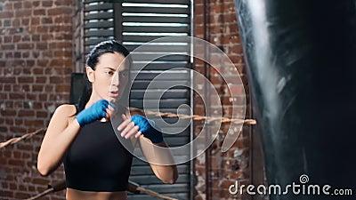 Poderosa morena hembra de combate punch y pateo en bolsa durante el entrenamiento en cámara lenta almacen de video