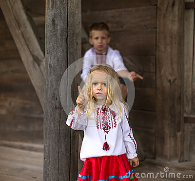 children in national ukrainian costumes. Old house