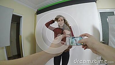 Point of View de un fotógrafo joven que toma imágenes de su novia modelo con un teléfono elegante metrajes