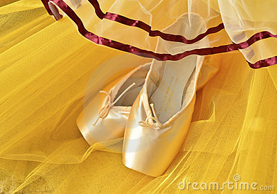 Pointe shoes and yellow tutu