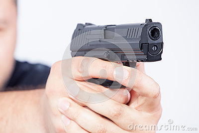 Pointing gun. Focus on the gun