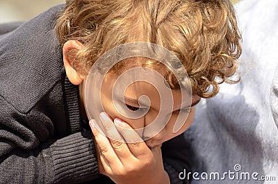 Pojke som gör en rolig framsida med handen