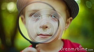 Pojke som ser till och med en förstoringsapparat