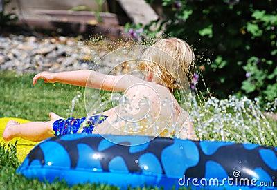 Pojkelekar som leker litet vatten