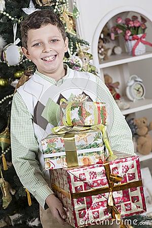 Pojken är lycklig med många julgåvor