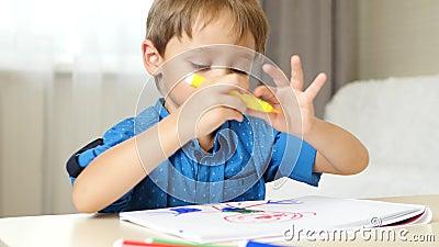 Pojken ritar med färgade markörer och föreställer sig en okänd hjälte Glad barndom Nöjd och skratt stock video