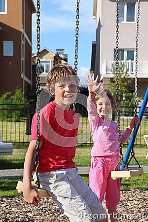 Pojken sitter på swing, och flickan vågr henne handen