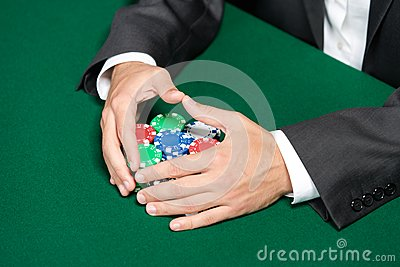 Poker player raking a big pile of poker chips