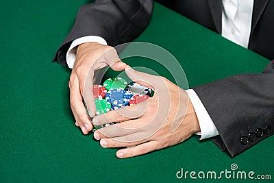 Poker player raking a big pile of poker chips