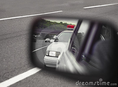 Police car viewed through sideview mirror