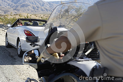 Police Officer On Motorbike Stopping Car On Desert Road
