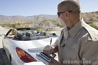 Police Officer Writing Traffic Ticket To Woman In Car