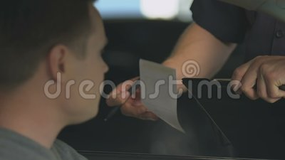 Policeman writing out fine to man for expired driving license, traffic offense. Stock footage stock footage
