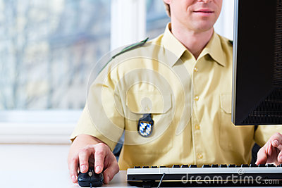 Polis som arbetar på skrivbordet i avdelning