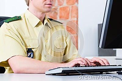 Politieman die aan bureau in afdeling werken