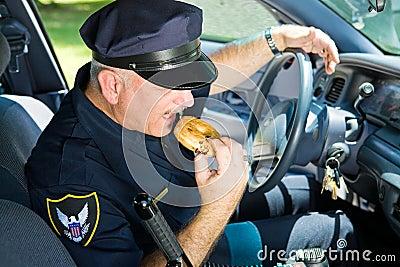 Politieman die Doughnut eet