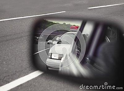 Politiewagen die door sideviewspiegel wordt bekeken