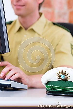 Polizeibeamte, der an Schreibtisch in der Station arbeitet