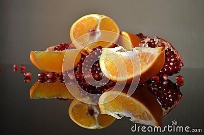 pomegranate-orange-wedges-slices-reflection-surface-table-50430005.jpg