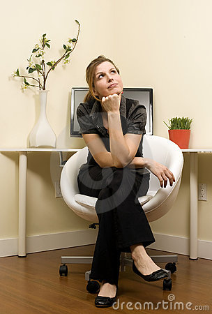 Pondering young Woman in Home Office