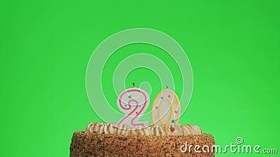 Poniendo una vela número veinte cumpleaños en una deliciosa tarta, pantalla verde 20 metrajes