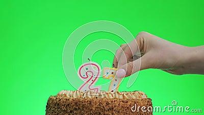 Poniendo una vela número veintisiete cumpleaños en una deliciosa tarta, pantalla verde 27 almacen de video