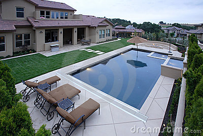 A pool with a waterfall in a luxury backyard