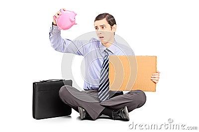 Poor businessman holding an empty piggybank and a piece of cardb
