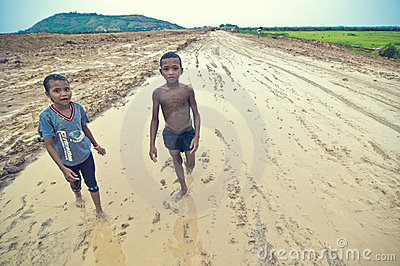Poor cambodian kids playing in mud Editorial Image