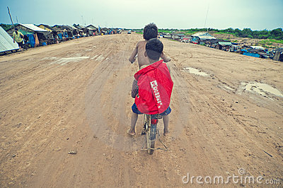 Poor cambodian kids racing with old bicycle Editorial Image
