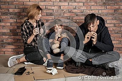 Poor homeless family sitting on floor Stock Photo