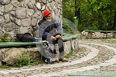 Poor man sitting on bench Editorial Image
