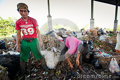 Poor people working in a scavenging at the dump Editorial Photo