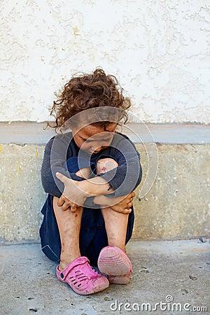 Poor, sad child against concrete wall