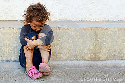 Poor, sad little child against the concrete wall