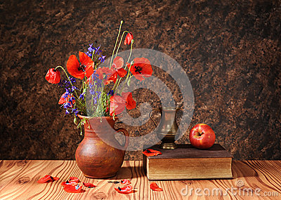 Poppy flower in a vase with an apple