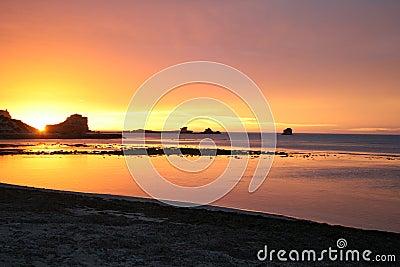 Por do sol alaranjado e cor-de-rosa em uma praia, Sul da Austrália