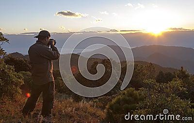 Por do sol da montanha do tiro do fotógrafo