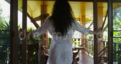 Porta aperta della donna e camminare fuori sul terrazzo che esamina Forest Landscape Back Rear View tropicale, ragazza castana at stock footage