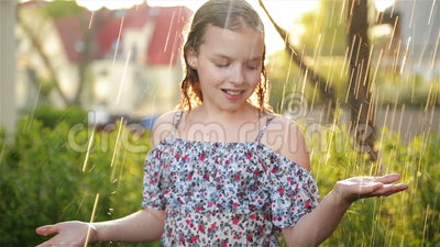 Portait of Adorable Little Girl Sta Giocando Felicemente Nella Pioggia Il Giorno Dell'Estate Calda stock footage