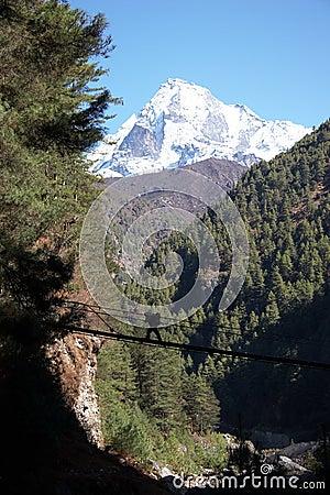 Porter crossing rope bridge in Himalaya, Nepal