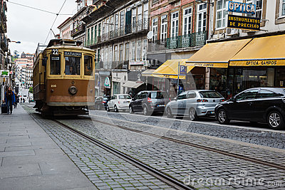 Porto, Portugal  street featuring an old brown and tan trolley on ancient cobblestones with a row modern cars Editorial Stock Image