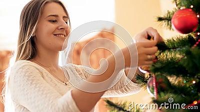 Porträt der glücklichen lächelnden jungen Frau, die schönen Flitter auf Niederlassung des Weihnachtsbaums am Morgen hängt stock footage