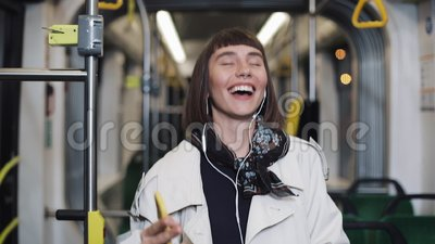 Porträt der jungen glücklichen Frau, die im Mantel mit den Kopfhörern öffentlich hören auf Musik und lustigen Transport des Tanze stock video footage