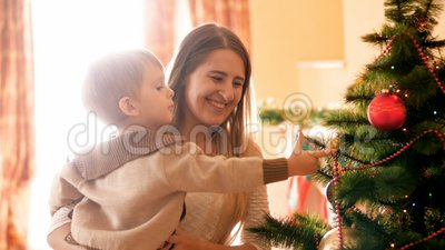 Porträt der jungen Mutter ihren kleinen Sohn unterrichtend, der Weihnachtsbaum mit Perlen und Flitter verziert stock footage